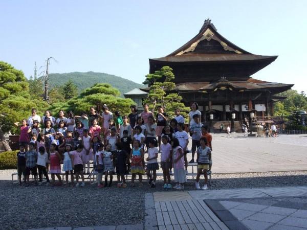 善光寺をバックに「花は咲く」を歌う地元の小学生