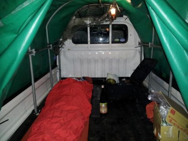 幌付きのトラックの荷台で車中泊