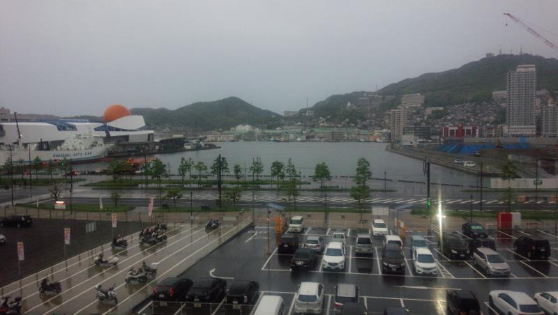 宿の窓から見える三菱重工の長崎造船所専用バイク駐輪場(雨)
